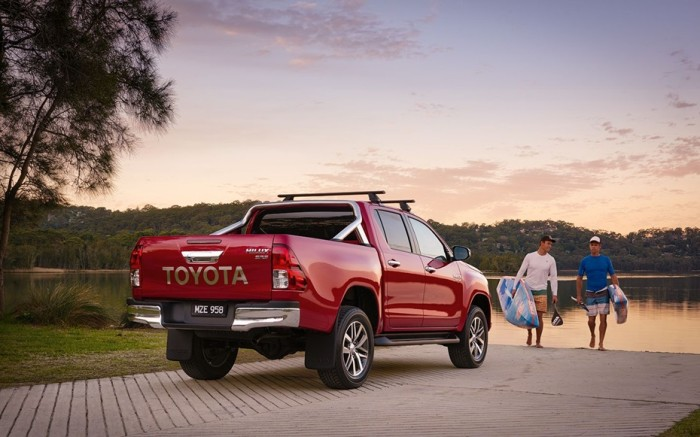A red toyota rental pickup truck parked at a lake.